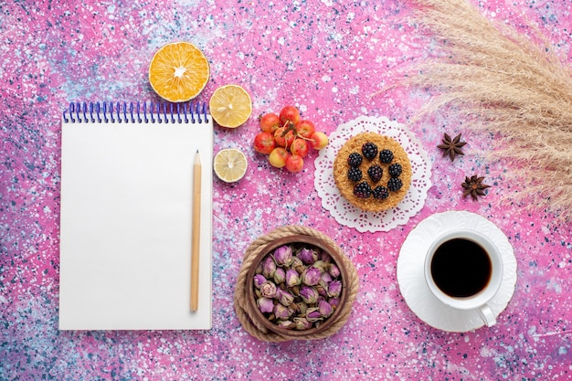 Top view cup of tea with little cake and notepad on the pink background.
