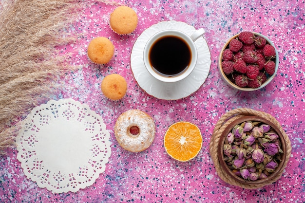 Top view of cup of tea with little cakes and fresh raspberries on pink surface