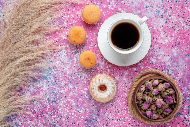 Top view of cup of tea with little cakes on pink surface