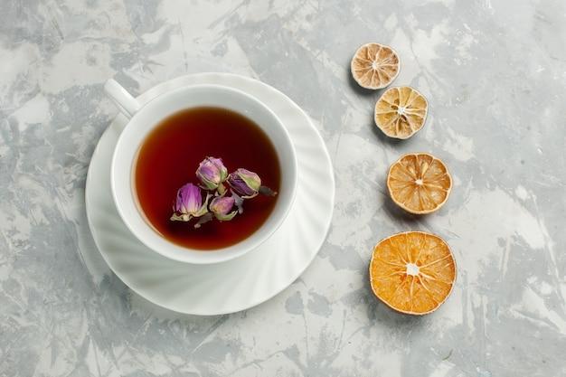 Vista dall'alto tazza di tè con piccoli fiori e limone sulla scrivania bianca
