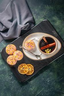 Vista dall'alto tazza di tè con piccoli biscotti dolci nel piatto e vassoio su sfondo scuro