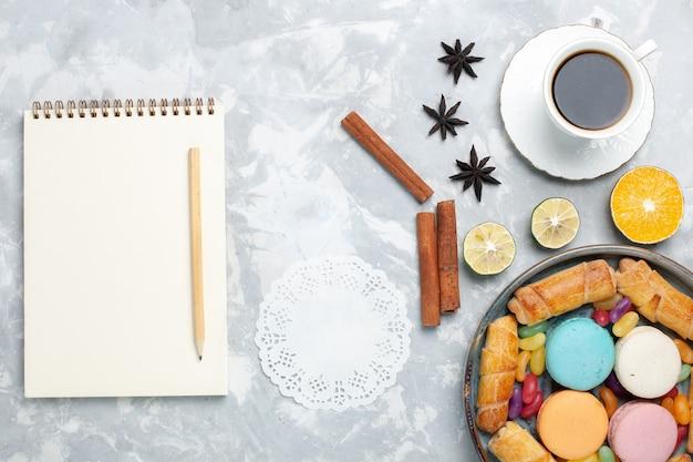 Vista dall'alto tazza di tè con bagel macarons su bianco