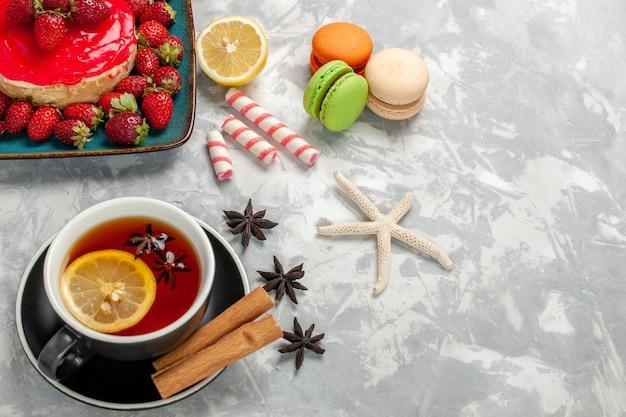 Vista dall'alto tazza di tè con macarons e piccola torta di fragole su superficie bianco chiaro