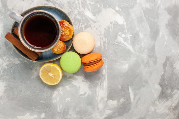 Top view cup of tea with macarons on white surface