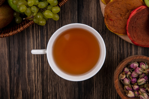 Top view a cup of tea with multi-colored pancakes on a stand and with green grapes on a wooden background