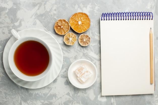 Tazza di tè vista dall'alto con blocco note sulla scrivania bianca