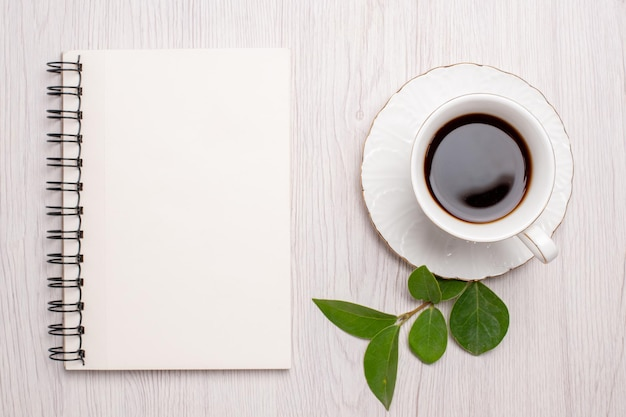 Vista dall'alto tazza di tè con blocco note sulla scrivania bianca zucchero tè biscotti dolce biscotto