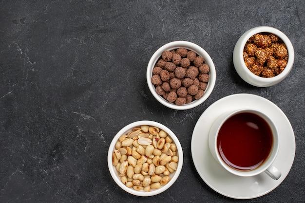 Vista dall'alto tazza di tè con noci e caramelle sullo spazio grigio scuro