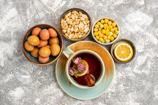 Top view of cup of tea with nuts and candies on light white surface