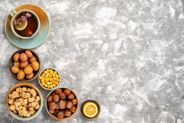 Top view of cup of tea with nuts and candies on white surface