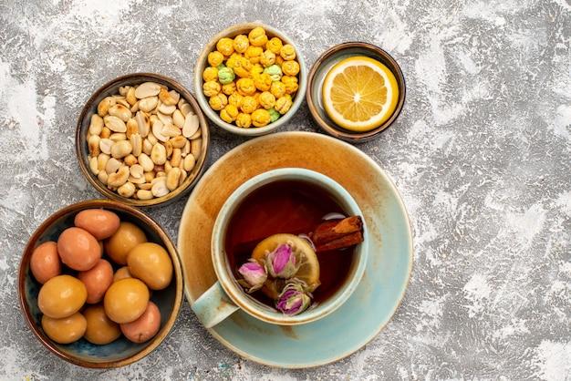 Vista dall'alto della tazza di tè con noci e caramelle sulla superficie bianca
