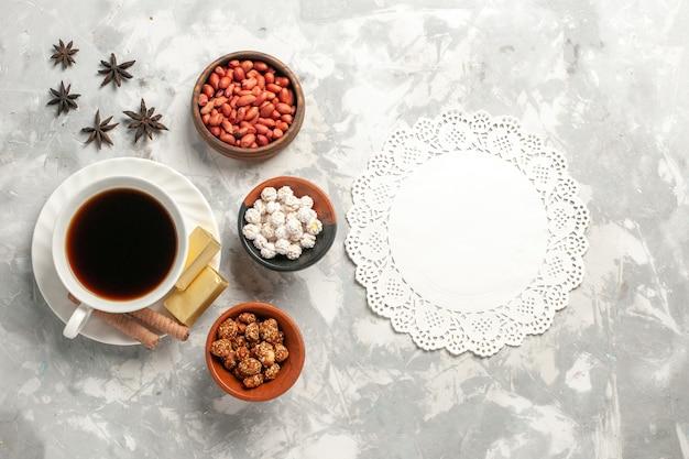 Vista dall'alto tazza di tè con noci e biscotti sulla superficie bianca