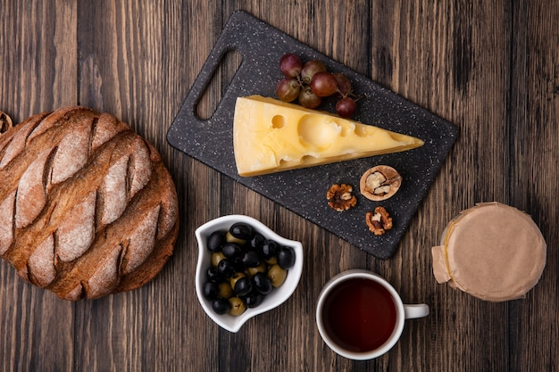 Top view cup of tea with olives in a saucer with maasdam cheese on a stand with yogurt and black bread on a wooden background