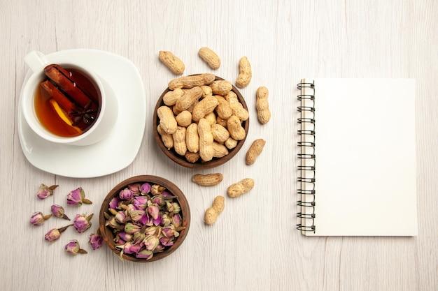Vista dall'alto tazza di tè con arachidi e fiori su uno spuntino al gusto di fiori di tè con noci da scrivania bianche