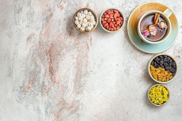 Vista dall'alto tazza di tè con uvetta e noci sulla superficie bianca cerimonia di uvetta dado di tè