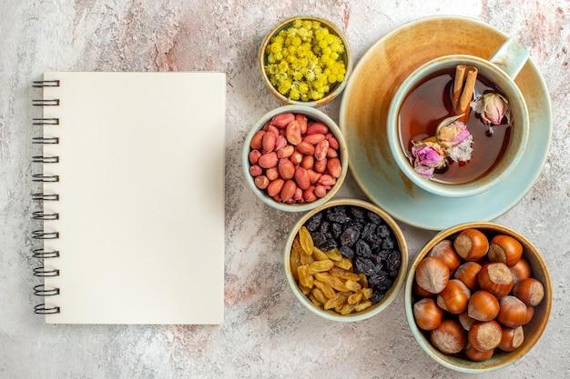 Vista dall'alto tazza di tè con uvetta e noci su cerimonia di uvetta di noci di tè di superficie bianca
