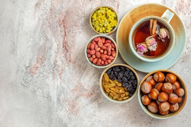 Vista dall'alto tazza di tè con uvetta e noci sulla superficie bianca cerimonia dell'uvetta con noci da tè