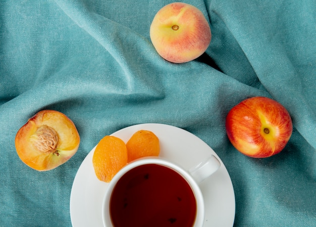 Top view of cup of tea with raisins on teabag and peaches on blue cloth surface