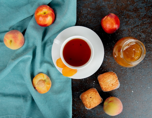 Top view of cup of tea with raisins on teabag and peaches on cloth with peach jam on black and brown surface