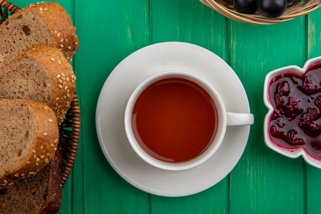 Top view of cup of tea with seeded brown cob slices and raspberry jam on green background