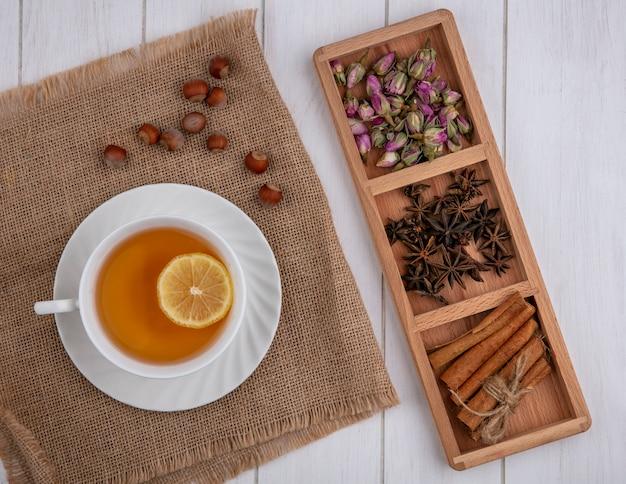 Tazza di tè vista dall'alto con una fetta di chiodi di garofano cannella limone e boccioli di rosa essiccati su uno sfondo grigio