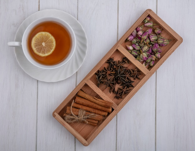 Top view cup of tea with a slice of lemon cinnamon cloves and dried rose buds on a gray background