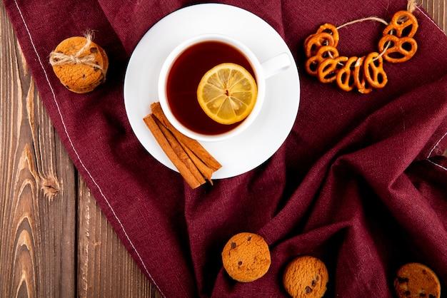 Vista dall'alto tazza di tè con una fetta di limone e cannella con biscotti su una tovaglia bordeaux