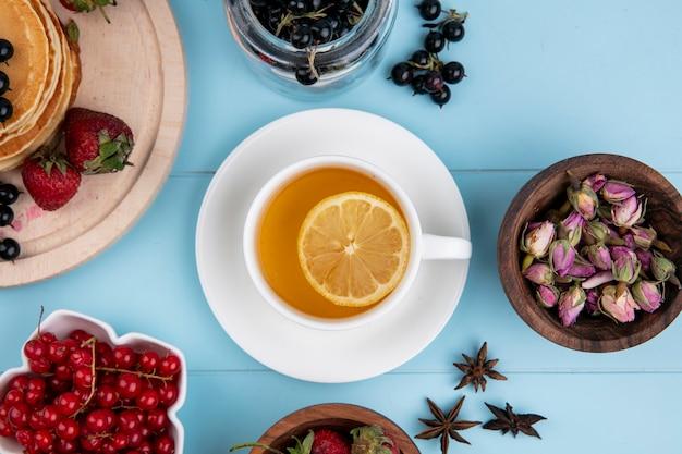 Vista dall'alto della tazza di tè con una fetta di limone con ribes rosso e nero e fragole su una superficie blu