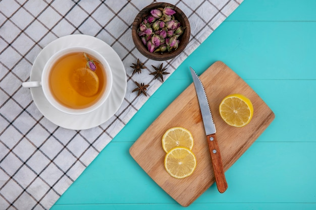 Top view cup of tea with sliced lemon on a board with a knife with dried flowers on a light blue background