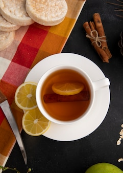 Top view cup of tea with sliced lemon and cinnamon with a knife on the table