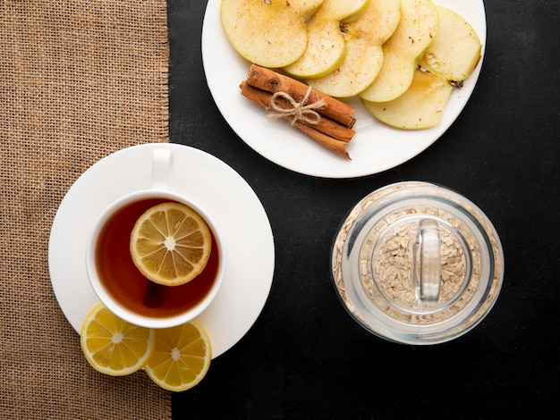 Top view cup of tea with slices of lemon and apple slices with cinnamon on a plate