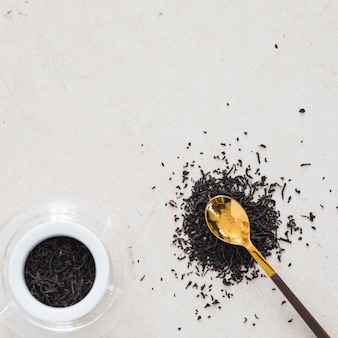 Top view cup of tea with spoon full of dry leaves