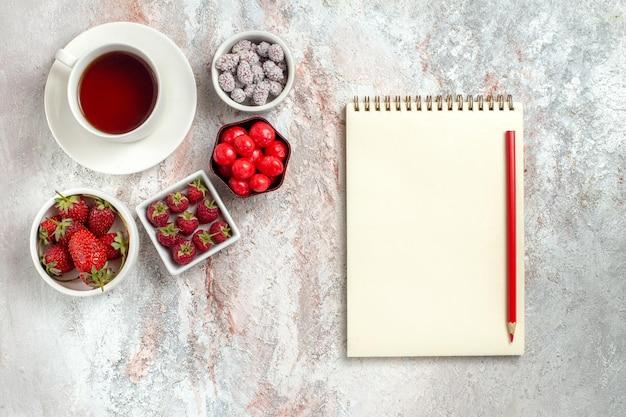 Vista dall'alto tazza di tè con fragole e caramelle su sfondo bianco frutta bacca tè zucchero candito