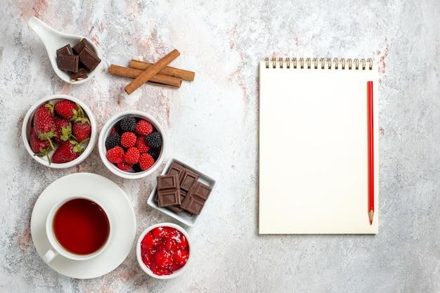 Vista dall'alto della tazza di tè con marmellata di fragole e confitures su superficie bianca