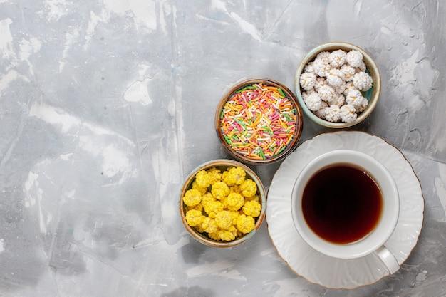 Vista dall'alto tazza di tè con confetture dolci sulla scrivania bianca