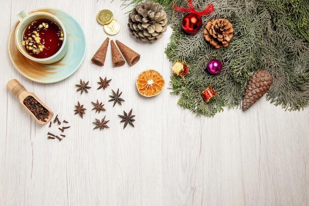 Vista dall'alto tazza di tè con giocattoli e albero su una pianta di sapore di fiori di tè da scrivania bianca