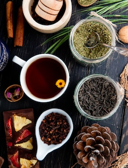 Top view of a cup of tea with various spices and herbs in glass jars on rustic