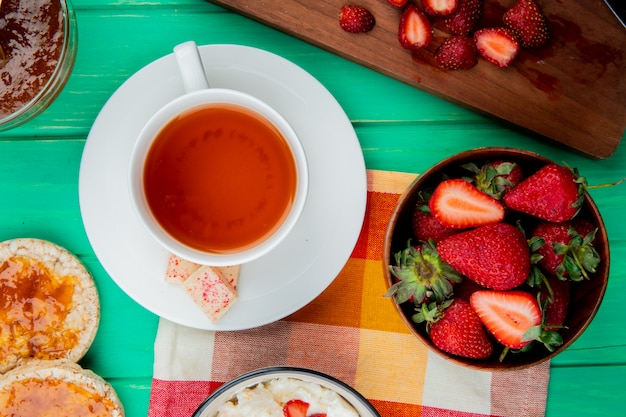 Top view of cup of tea with white chocolate on teabag and bowl of strawberries with crispbreads and peach jam on green surface