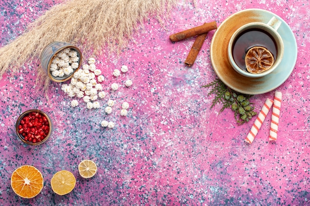 Top view cup of tea with white sweet confitures and cinnamon on light-pink surface