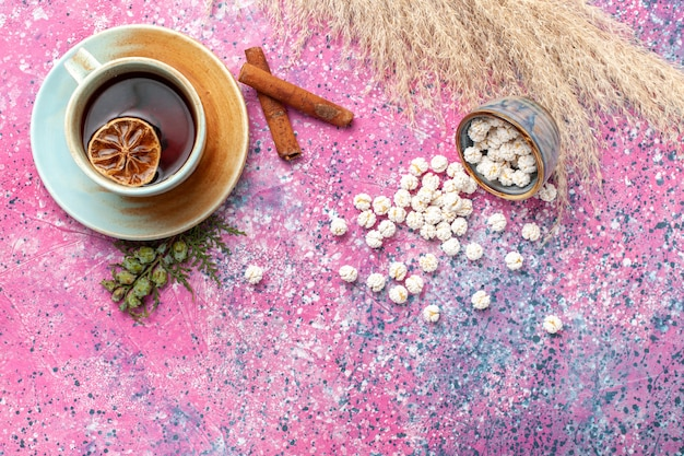 Top view cup of tea with white sweet confitures and cinnamon on light pink surface