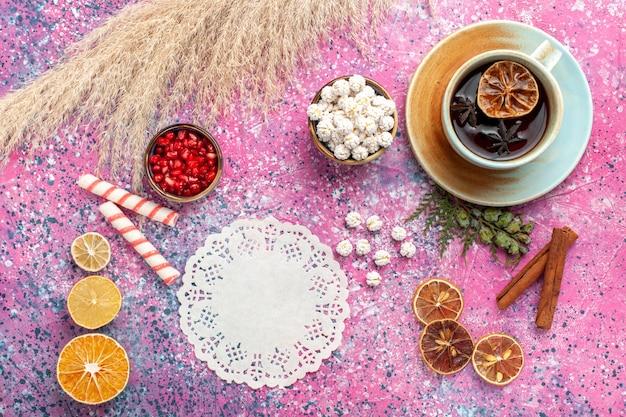 Vista dall'alto tazza di tè con confetture dolci bianche e cannella sulla scrivania rosa
