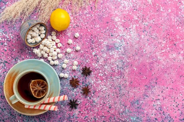 Vista dall'alto tazza di tè con confetture dolci bianche e limone sulla superficie rosa