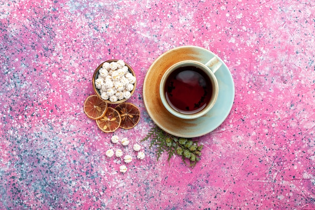 Top view cup of tea with white sweet confitures on the pink surface