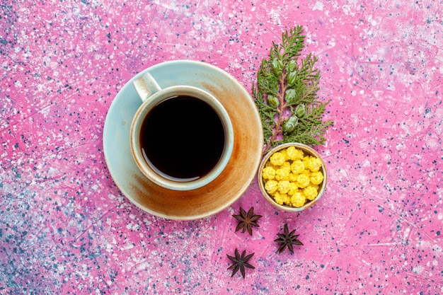 Top view cup of tea with yellow candies on pink desk