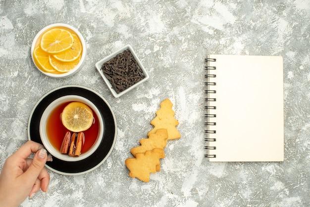 Vista dall'alto una tazza di tè nella ciotola di biscotti a mano della donna con il taccuino di fette di limone e cioccolato sulla superficie grigia