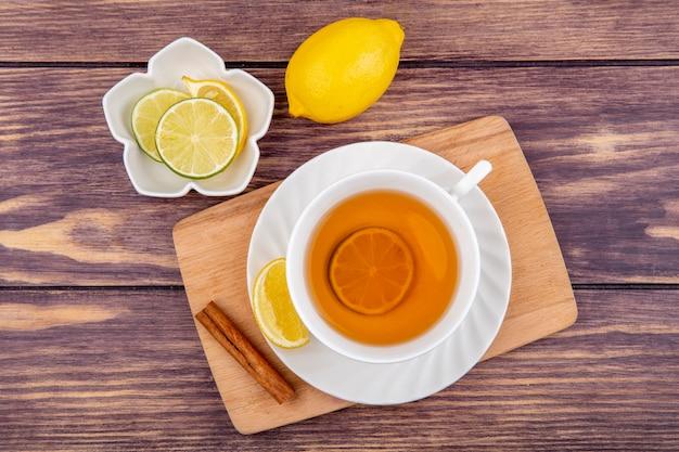 Vista dall'alto di una tazza di tè sulla tavola di cucina in legno con fette di limone con bastoncini di cannella su legno