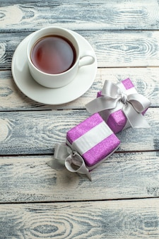 Top view a cup of tea xmas gifts on wooden background