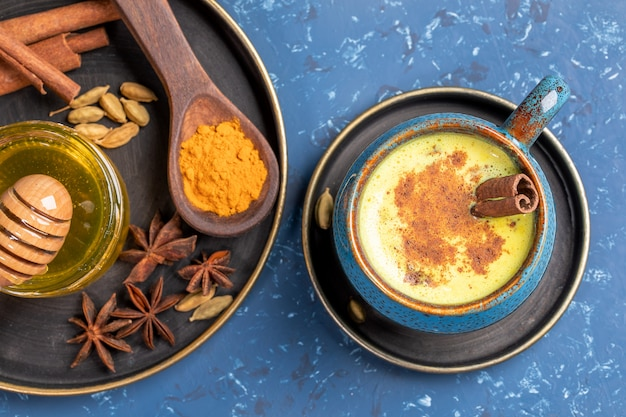 Top view of cup of traditional indian ayurvedic golden turmeric milk and plate with ingredients on blue background.