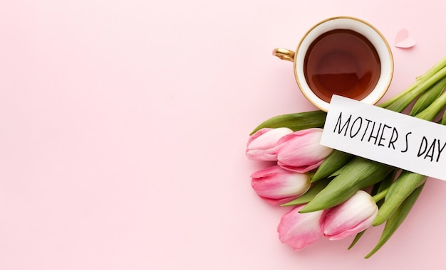 Top view cup with tea beside tulips