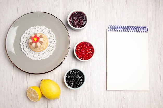 Cupcake vista dall'alto e piatto di marmellata di cupcake appetitoso sul centrino di pizzo accanto al quaderno bianco ciotole di semi di marmellate di melograno e limone sul tavolo